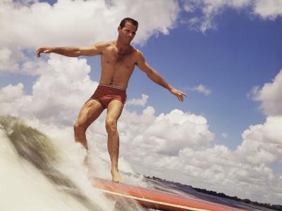 Man Riding Surf Board-Dennis Hallinan-Photographic Print