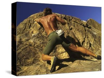 Man Rock Climbing Without Equipment