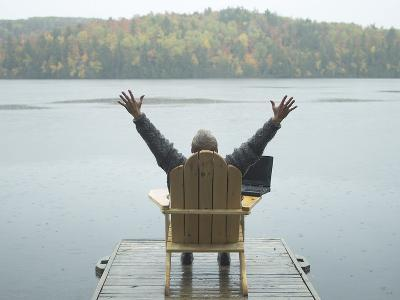 Man Sitting on a Dock with Arms Outstretched--Photographic Print