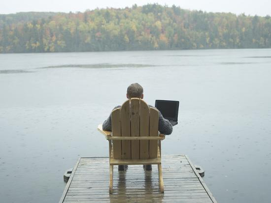 Man Sitting on a Dock Working on Laptop--Photographic Print