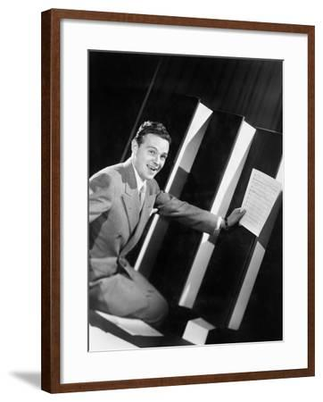 Man Sitting with Oversized Books Holding Sheet Music in His Hands--Framed Photo