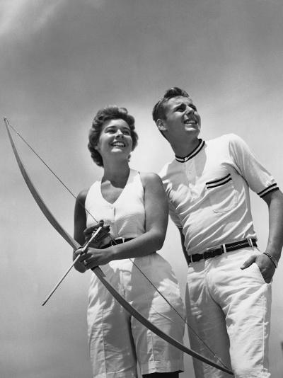 Man Standing Beside Woman Who is Holding Bow and Arrow--Photographic Print