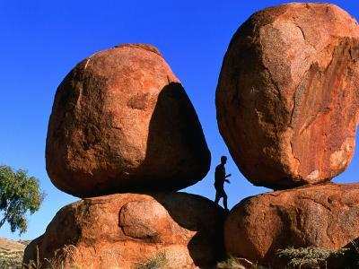 Man Standing in Between Boulders, Devil's Marbles Conservation Reserve, Australia-John Banagan-Photographic Print