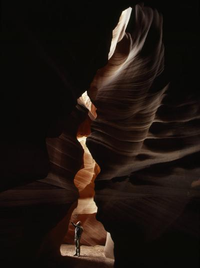 Man Standing in Sunlight in a Narrow Slot Canyon-Paul Chesley-Photographic Print