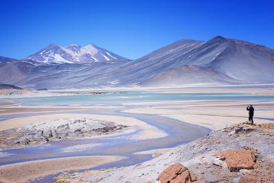 Man Standing on Rocks Looking over Miscanti Laguna, Turquoise Mineral Lake, San Pedro De Atacama-Kimberly Walker-Photographic Print