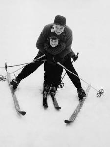 Man Teaching Boy To Ski