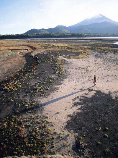 Man Walking on Dry Lake Bed with Llaima Volcano in Distance, Conguillio National Park, Chile-Aaron McCoy-Photographic Print
