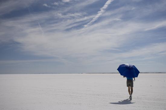 Man Walking With Blue Umbrella On The Bonneville Salt Flats-Lindsay Daniels-Photographic Print