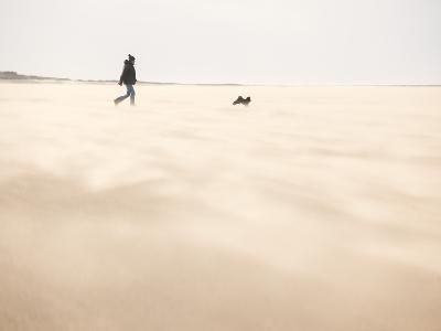 Man Walking with Dog across a Windy Beach-Craig Easton-Photographic Print
