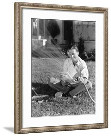 Man Watering the Grass and Reading--Framed Photo