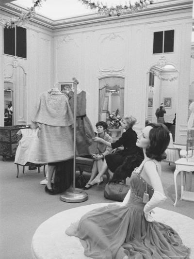 Mannequin Wearing Evening Gown As Women Admire Dresses In Background