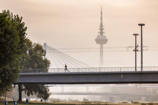 Mannheim, Baden-Württemberg, GER: Male Running Over Bridge Crossing River Neckar On Foggy Morning-Axel Brunst-Photographic Print