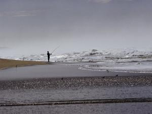 A Fisherman Casts His Line into the Surf by Marc Moritsch