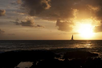 A Sailboat Among Gentle Waves at Sunset