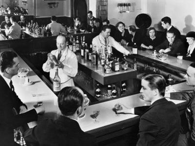 Bartender Prepares a Drink as Patrons Enjoy Themselves at Popular Speakeasy during Prohibition