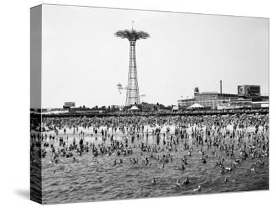Bathers Enjoying Coney Island Beaches. Parachute Ride and Steeplechase Park Visible in the Rear