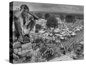 Boy Sitting on Rock Ledge Above Refugee Camp by Margaret Bourke-White