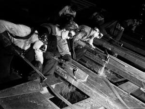 """Female """"Burners"""" Using Acetylene Torches to Bevel Armor Plate For Tanks at Steel Works by Margaret Bourke-White"""