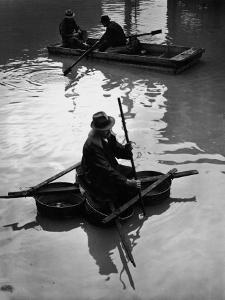 Flood Victim Paddling Boat Fashioned Out of Four Washtubs in the Flood Waters of Mississippi River by Margaret Bourke-White