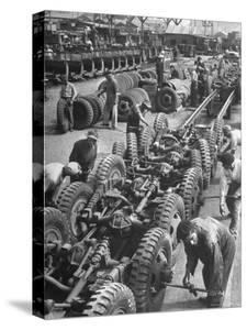 French Army Mechanics Busy Assembling Tires on the Chassis of 3/4 Ton American Made Army Trucks by Margaret Bourke-White