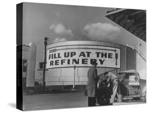 Gas Station Attendant Changing Oil for a Customer Next to Fill Up at the Refinery Sign by Margaret Bourke-White