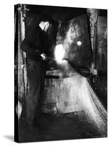 Glass Blower Heating Up Molten Glass Prior to Blowing a Glass Piece at Corning Glass Plant by Margaret Bourke-White