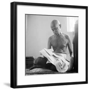 Indian Leader Mohandas Gandhi Reading as He Sits Cross Legged on Floor, at Home by Margaret Bourke-White