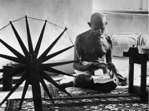 Indian Leader Mohandas Gandhi Reading as He Sits Cross Legged on Floor by Margaret Bourke-White