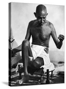 Indian Leader Mohandas Gandhi Using His Spinning Wheel in Bungalow at His Nature Clinic by Margaret Bourke-White