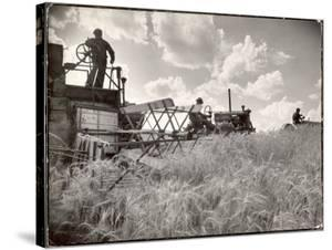 Kansas Farmer Driving Farmall Tractor as He Pulls a Manned Combine During Wheat Harvest by Margaret Bourke-White