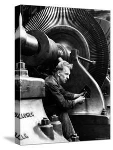 Laborer Tightening Bolt Next to Large Piece of Machinery by Margaret Bourke-White