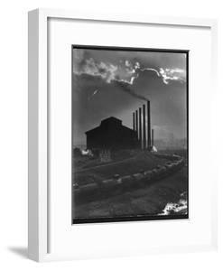 Massive Otis Steel Mill Surrounded by Tanker Cars on Railroad Track on a Cloudy Day by Margaret Bourke-White