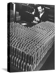 Rows of 15 cm Shells on Table Where Worker Uses Hammer and Stamping Tool at Skoda Munitions Factory by Margaret Bourke-White