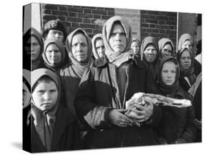 Russian Woman Grimly Holding a Slab of Meat as Other Peasant Women Staunchly Stand by in Siberia by Margaret Bourke-White