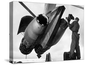 SAC's Maintenance Mechanic Sliding Into Barrel of Bomber's Jet Engine with the Help of His Partner by Margaret Bourke-White