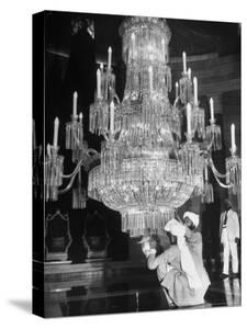 Servants of British Lord Archibald Wavell cleaning Crystal Chandelier in Opulent Palace by Margaret Bourke-White