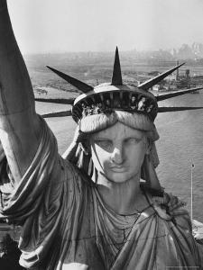 Sightseers Hanging Out Windows in Crown of Statue of Liberty with NJ Shore in the Background by Margaret Bourke-White