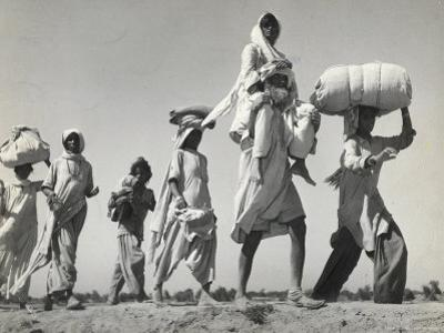 Sikh Carrying His Wife on Shoulders After the Creation of Sikh and Hindu Section of Punjab India by Margaret Bourke-White