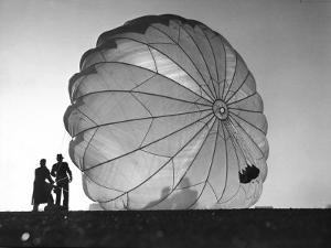 Two Irving Air Chute Co. Employees Struggling to Pull Down One of their Parachutes after Test Jump by Margaret Bourke-White