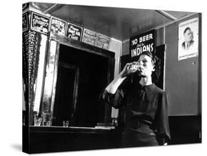 Woman Drinking under Sign, No Beer Sold to Indians, Katherine's Place, Happy Hollow, Fort Peck Dam by Margaret Bourke-White