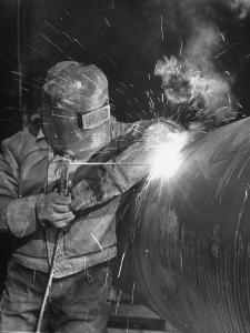 Worker Welding Pipe Used in Natural Gas Pipeline at World's Biggest Coal Fueled Generating Plant by Margaret Bourke-White