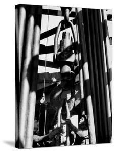 Workers Lower Pipe into Oil Well Inside Rig in a Texaco Oil Field by Margaret Bourke-White