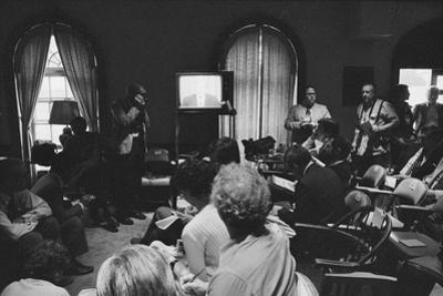 Reporters watch President Carter making TV announcement on aborted Iran rescue, 1980