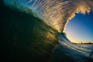 Sunset back lights a tubing wave by Mark A Johnson