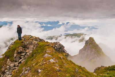 Woman high atop cloudy Harbor Mountain, Sitka, Alaska by Mark A Johnson