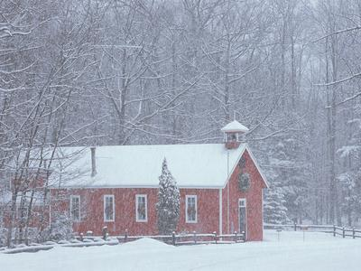 Old Red Schoolhouse and Forest in Snowfall at Christmastime, Michigan, USA