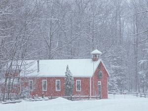 Old Red Schoolhouse and Forest in Snowfall at Christmastime, Michigan, USA by Mark Carlson