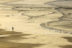 Woman Jogging at Sunrise on Gwithian Beach, Cornwall, England, United Kingdom by Mark Chivers