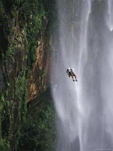 Climber Dangles on Rope Near a Waterfall in Nordeste, Brazil by Mark Cosslett