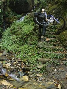 Woman Carries Mountain Bike up Steep Stone Stairs Next to Stream by Mark Cosslett
